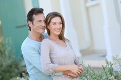 Paare von mittlerem Alter, die vor ihrem Haus schauen Lizenzfreie Stockfotografie