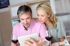 Paare von mittlerem Alter im trinkenden Wein der Küche Stockfotos