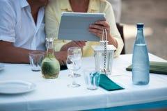 Paare von mittlerem Alter unter Verwendung einer Tablette am Tisch Stockbild