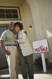 Paare von mittlerem Alter vor neuem Haus Lizenzfreies Stockfoto