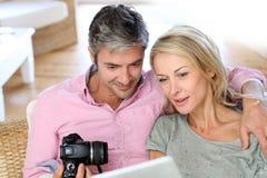 Paare von mittlerem Alter zu Hause unter Verwendung des Laptops und der Kamera Stockfoto