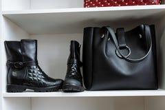 Paare von schwarzen Lederschuhen mit flachen Abs?tzen und von schwarzen Tasche auf einem wei?en Regal im Speicher stockbilder