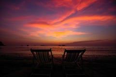 Paare von Sonnenruhesesseln auf dem Strand während der Dämmerung relax stockfotografie