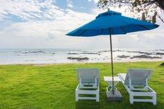 Paare von Sonnenruhesesseln und von Strandschirm auf einem einsamen Strand, perfektes Ferienkonzept stockbilder