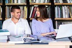 Paare von Studenten in einer Bibliothek Mann und Frau, die in der Bibliothek studieren stockbild