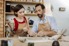 Paare von Töpfern bei der Herstellung von netten braunen Schalen lizenzfreies stockfoto