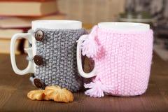 Paare von Teeschalen mit gestrickten Abdeckungen und Keksen Stockbilder