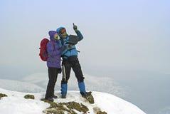 Paare von Wanderern auf einer Winterbergspitze mit einem Laptop Stockbild