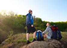 Paare von Wanderern mit den Rucksäcken, die auf ihrer Weise stillstehen Reise, VA stockbild