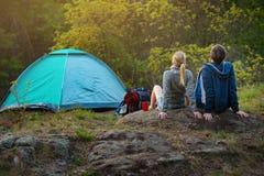 Paare von Wanderern mit den Rucksäcken, die sich vorbereiten, ihr jour fortzusetzen stockfotografie