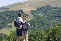 Paare von Wanderern mit den Rucksäcken, die am Standpunkt und am enjoyi stehen Lizenzfreie Stockfotografie