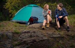 Paare von Wanderern mit Rucksäcken und von heißem Tee am frühen Morgen Tr Stockfoto