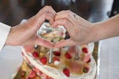 Paare vor dem Kuchen, der ein Herz mit den Händen macht Lizenzfreies Stockbild