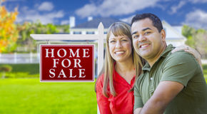 Paare vor für Verkaufs-Zeichen und Haus Stockfotos