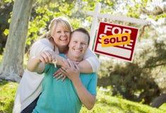 Paare vor Verkaufs-Real Estate-Zeichen, das Schlüssel hält Stockbild