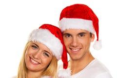Paare am Weihnachten mit Weihnachtsmann-Hüten Lizenzfreie Stockfotografie