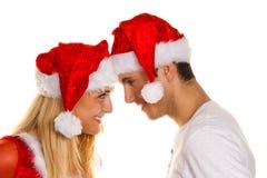 Paare am Weihnachten mit Weihnachtsmann-Hüten Stockbild