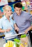 Paare, welche die Einkaufsliste und die ausgesuchten Produkte besprechen Stockfoto
