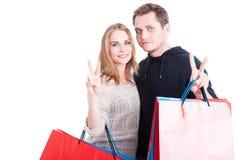 Paare, welche die Einkaufstaschen machen Friedensgeste halten Stockbild