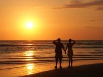 Paare, welche die Einstellungssonne überwachen Lizenzfreie Stockfotos