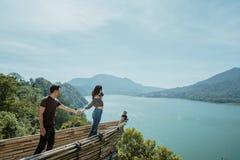 Paare, welche die Hand genießt Natur von der Bergkuppe halten stockbild