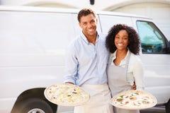 Paare, welche die Pizza steht in Front Of Van liefern stockbilder