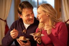 Paare, welche die Scheibe des Kuchens sitzend auf Sofa genießen stockbild