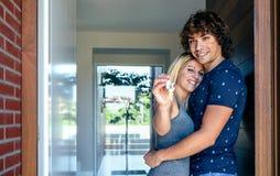 Paare, welche die Schlüssel ihres Hauses zeigen stockbilder