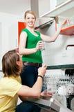 Paare, welche die Spülmaschine leeren Lizenzfreies Stockfoto