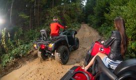 Paare, welche die vierrädrigen Droschken ATV nicht für den Straßenverkehr fahren Lizenzfreies Stockfoto