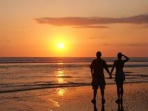 Paare, welche Hand in Hand die Einstellungssonne überwachen Lizenzfreies Stockfoto