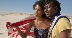 Paare wickelten in der amerikanischen Flagge ein, die zusammen auf dem Strand 4k sitzt stock video footage
