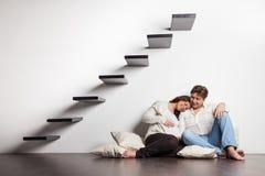 Paare zu Hause, die auf Treppen sitzen Schwangerschaft stockfotografie