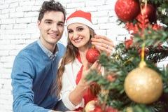 Paare zu Hause, die Baum für Weihnachten verzieren lizenzfreies stockbild