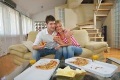 Paare zu Hause, die Pizza essen stockfoto