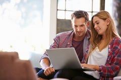 Paare zu Hause im Aufenthaltsraum unter Verwendung der Laptop-Computers stockfoto