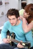 Paare zu Hause mit einer Gitarre Stockfotografie