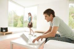 Paare zu Hause unter Verwendung der Technologie Stockbild