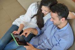 Paare zu Hause unter Verwendung des Tablet-Computers Stockbild