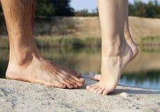 Paarfüße, die nahe See küssen Stockfotografie