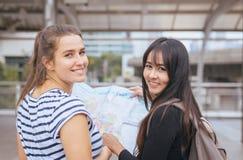Paarfrauen-Holdingstadtplan des Porträts schöner und Gehen in die Stadt, weibliches Vertrauen glücklich und Lächeln, Lebensstilko lizenzfreie stockfotos
