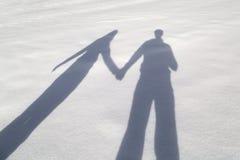 Paarhändchenhalten im schneebedeckten Weg lizenzfreie stockbilder