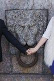 Paarhändchenhalten vor dem hintergrund eines Granitlöwes Stockfoto