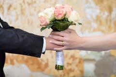 Paarhände, die den Blumenstrauß einer Braut halten Stockbilder