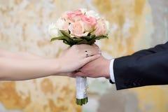 Paarhände, die den Blumenstrauß einer Braut halten Stockfotografie