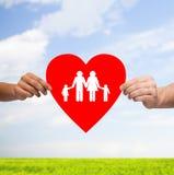 Paarhände, die rotes Herz mit Familie halten Stockbilder