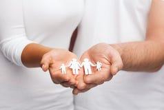 Paarhände mit Papiermannfamilie Stockbilder