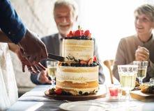 Paarhanden die Huwelijkscake snijden stock fotografie
