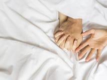 Paarhanden die witte bladen in vervoering, orgasme trekken Concept hartstocht orgasme Erotische ogenblikken vertrouwelijk concept stock afbeelding