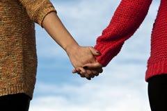 Paarholding überreicht blauen Hintergrund Stockfoto
